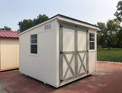 A white lean-to style shed with gray framing details on the doors